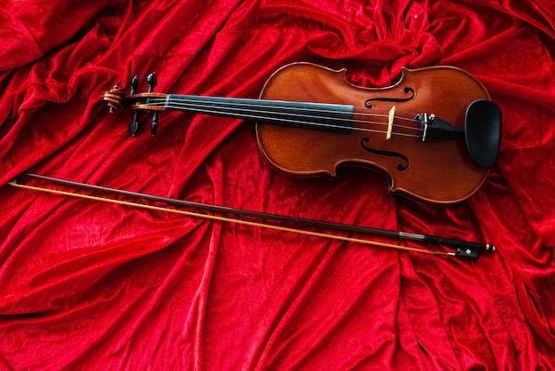 The classic violin and bow put on red cloth background,show detail of the instrument Premium Photo