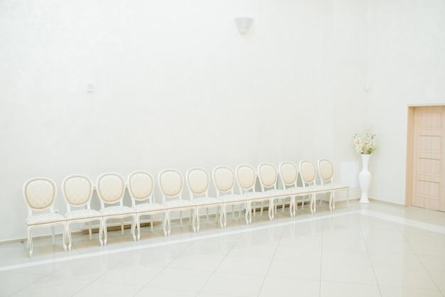 明るい部屋、ホールに並んでいる古典的な白い椅子 Premium写真
