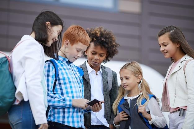 屋外で携帯電話を使用しているクラスメート Premium写真