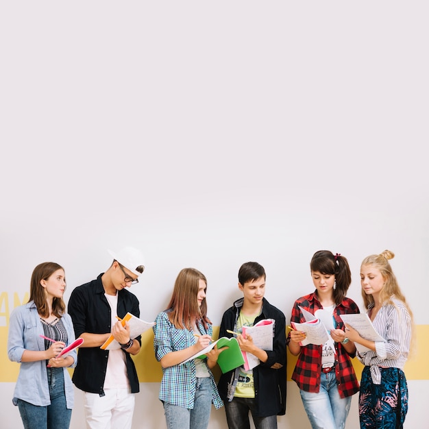 classmates with books at wall photo free