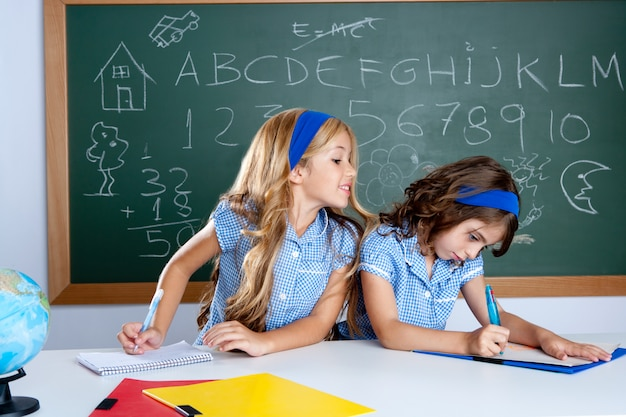 Classroom with two kids students cheating on test Photo