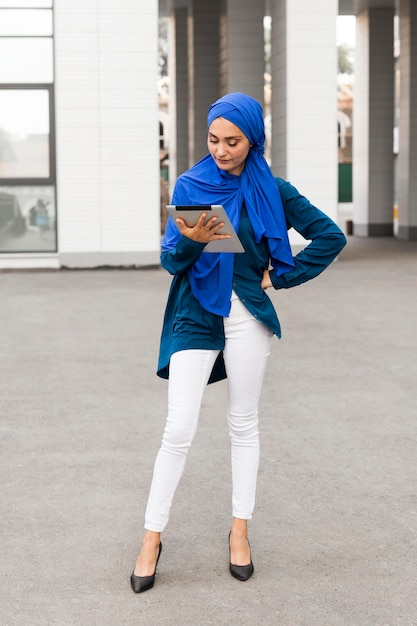 Classy teenager with hijab looking on her tablet Free Photo