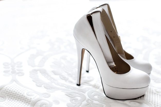 Classy white platform shoes stand on white embroidered cloth Free Photo