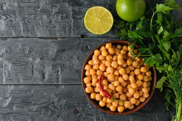 Clay bowl filled with boiled chickpeas on a black wooden table with parsley and lime. vegetarian cuisine from legumes. the view from the top. flat lay. Premium Photo