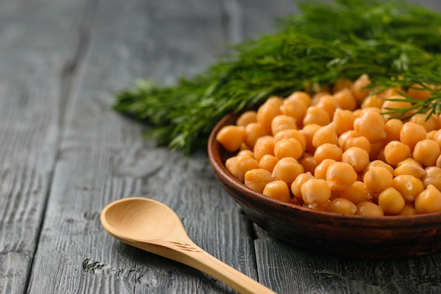 Clay bowl with boiled chickpeas and herbs on a black wooden table. vegetarian cuisine from legumes. Premium Photo