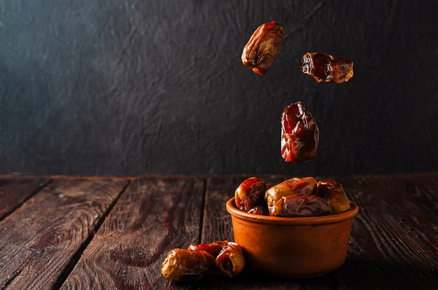 Clay brown bowl with dried dates on a wooden table. healthy sweets, healthy nutrition. traditional dessert in ramadan. Premium Photo