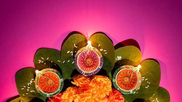 Clay diya lamps lit during dussehra with yellow flowers, green leaf and rice Premium Photo