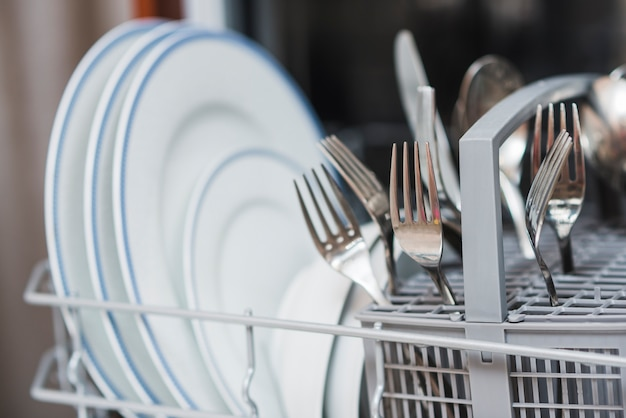 Clean dishes in washing machine Premium Photo