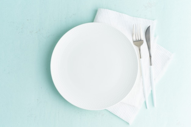 Clean empty white plate, fork and knife on green blue turquoise stone table, copy space Premium Photo