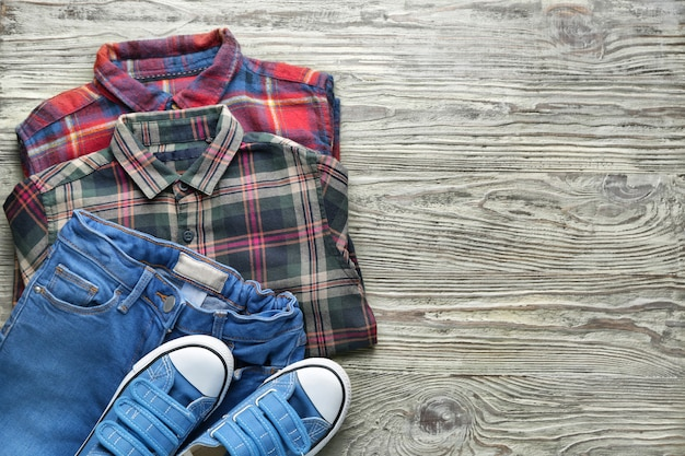 Clean kid clothes with shoes on table Premium Photo