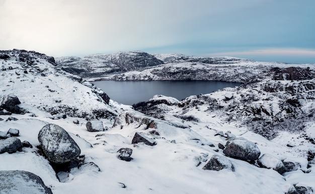 깨끗한 산 호수, 탁 트인 겨울 전망. 높은 고도의 얼어 붙은 호수가있는 놀라운 북극 풍경. 프리미엄 사진