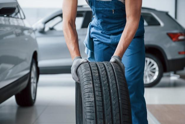 クリーンルーム。修理ガレージでタイヤを保持しているメカニック。冬用および夏用タイヤの交換 無料写真