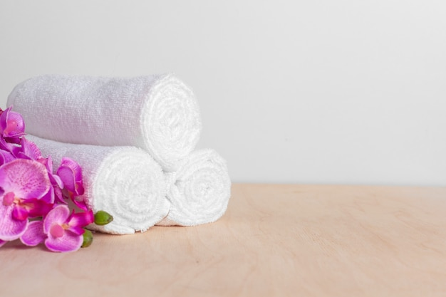 Clean soft towels with flower on wooden table Premium Photo