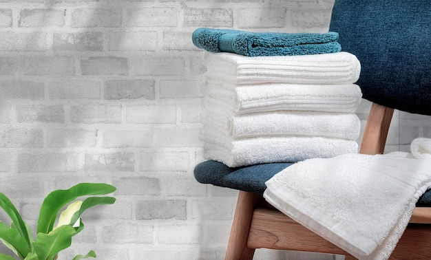 Clean terry towels on wooden chair with brick wall background, copy space. Premium Photo
