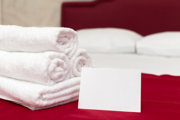 Clean towels on bed at hotel room Premium Photo