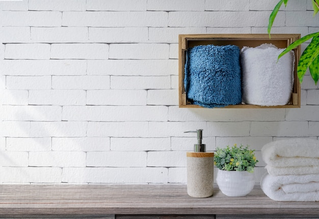 Clean towels with soap dispenser on shelf and wooden table in bathroom, white brick wall background Premium Photo