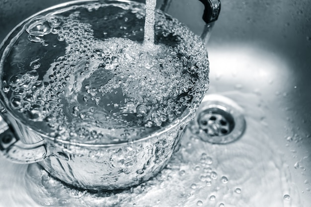 Clean water in the kitchen sink, water rinse in pot waste in household. Premium Photo