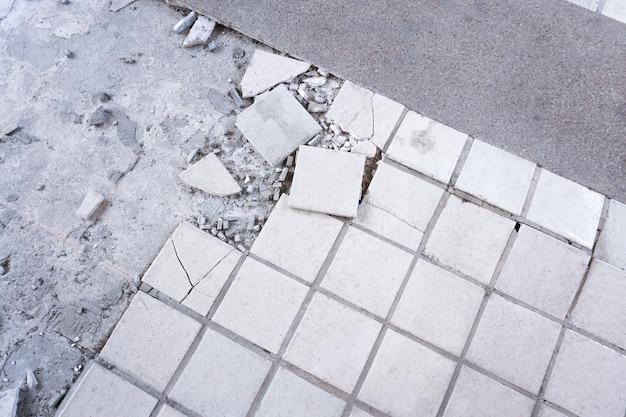 Чистая белая сломанная плитка стены текстуры фона. плиточный пол взорвался и потрескался, потому что использовался в течение долгого времени, ремонт плитки в доме Premium Фотографии