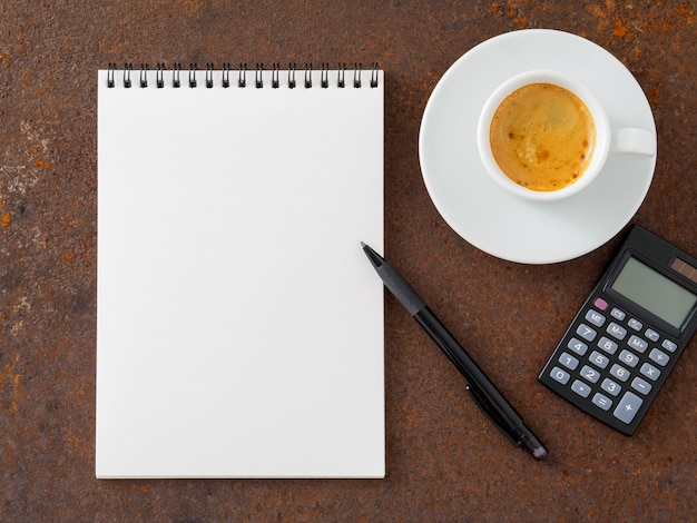 Clean white sheet in an open spiral-bound pad, pen, calculator and cup of coffee on the iron Premium Photo