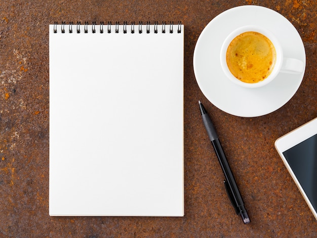 Clean white sheet in an open spiral-bound pad, pen, mobile phone and cup of coffee on the iron Premium Photo