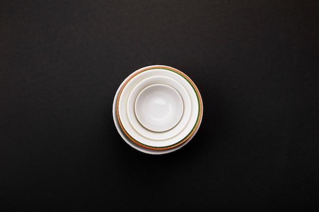 Clean white tableware on black. top view Premium Photo