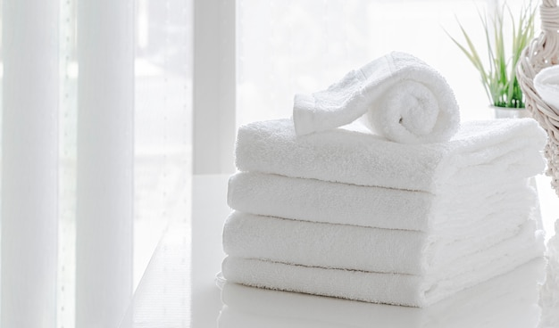 Clean white towels on white table in white room, copy space. Premium Photo
