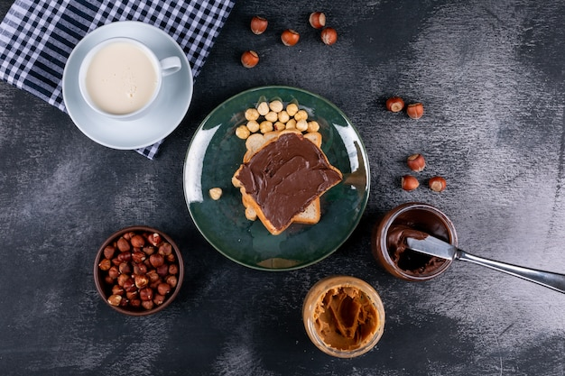 Cleaned and shelled hazelnuts in a green glassy plate with cocoa spread bread, milk flat lay on a dark stone table Free Photo