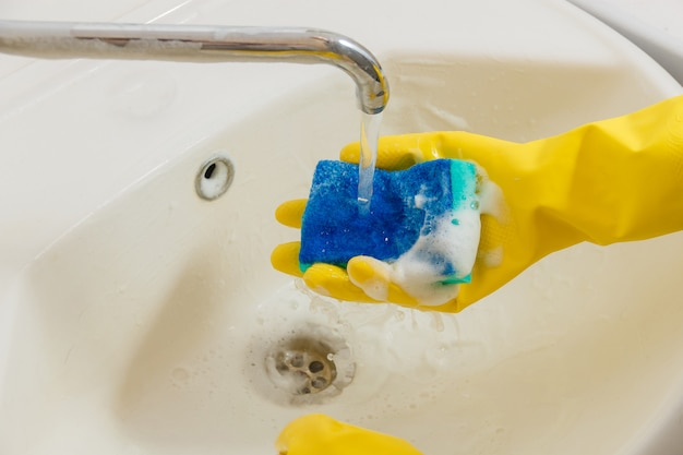 Cleaning bathroom faucet with detergent in yellow rubber gloves with blue sponge Premium Photo