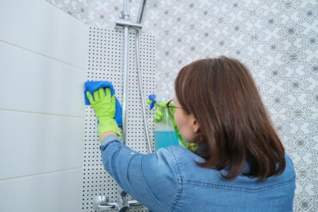 バスルームの掃除、ぼろきれと洗剤の手袋をした女性、シャワーの洗濯と磨き、ガラス、蛇口、タイル張りの壁 Premium写真