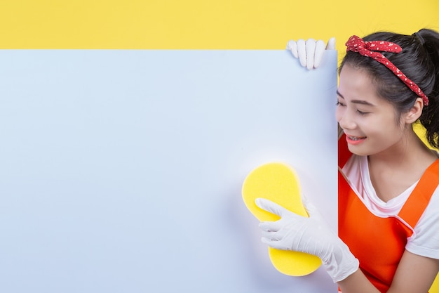 Cleaning . a beautiful woman holds a white board to put an advertisement message and hold cleaning equipment on a yellow . Free Photo