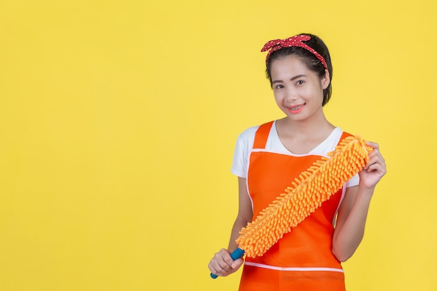 Cleaning . a beautiful woman with a cleaning device on a yellow . Free Photo