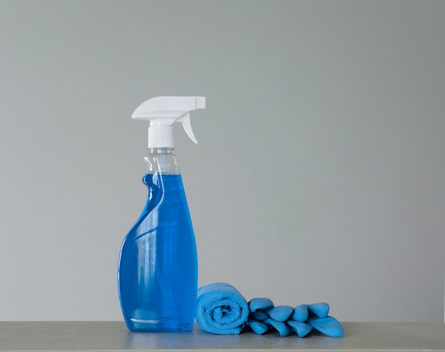 Cleaning blue spray bottle with plastic dispenser, marigolds and cloth for dust on grey background Premium Photo