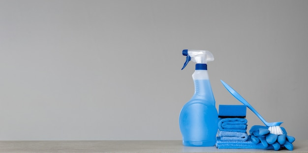 Cleaning blue spray bottle with plastic dispenser, sponge, scrubbing brush for dish, cloth for dust and rubber gloves on grey Premium Photo