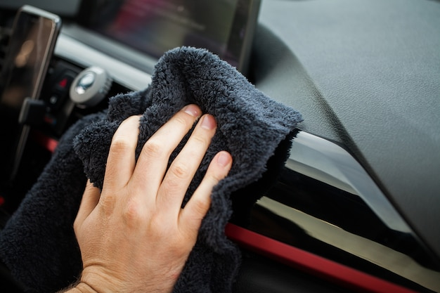Cleaning car. hand with microfiber cloth cleaning car interior Premium Photo