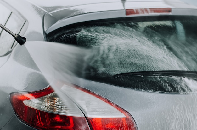 Cleaning car using high pressure water. Premium Photo