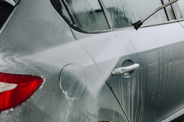 Cleaning car using high pressure water. Premium Photo