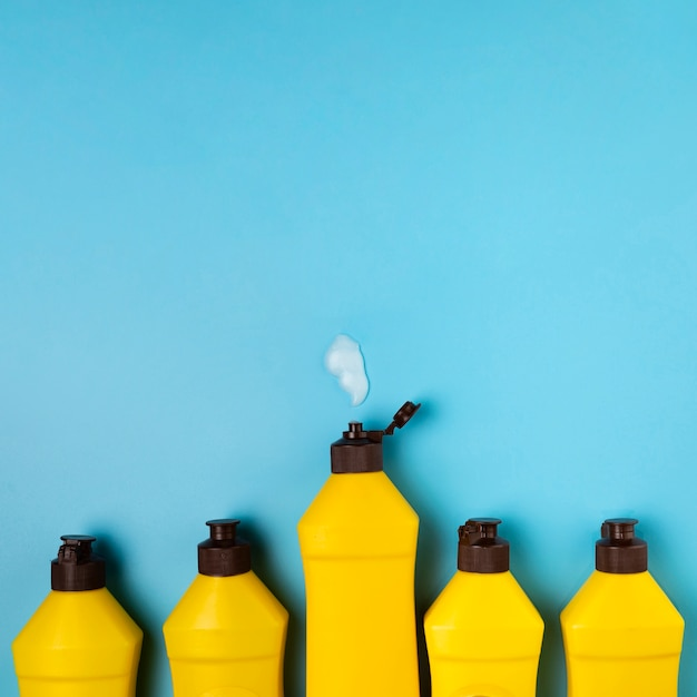 Cleaning concept with yellow detergent bottles Free Photo