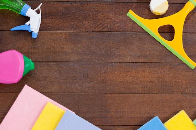 Cleaning equipments arranged on wooden floor background Premium Photo