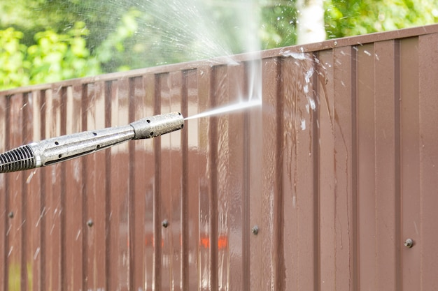 Cleaning fence with high pressure power washer Premium Photo