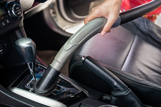 Cleaning modern car interior with vacuum cleaner. handle vacuum Premium Photo