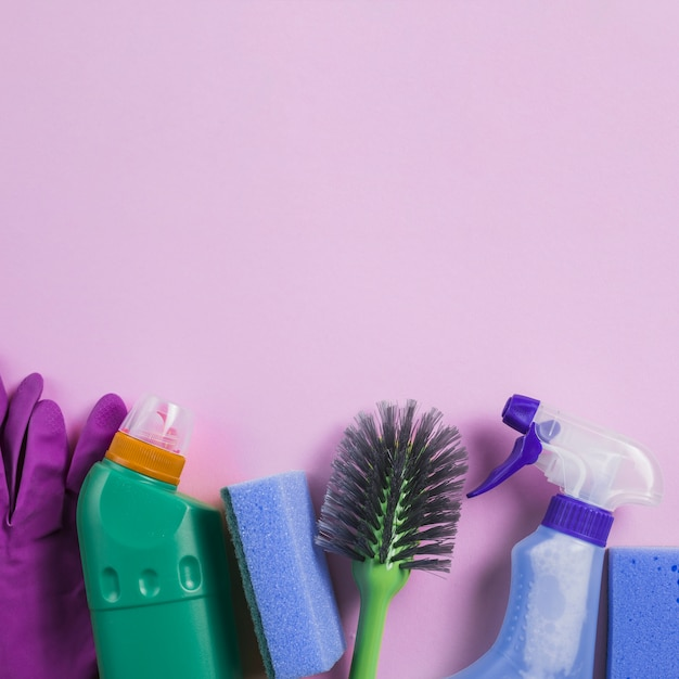 Cleaning products at the bottom of pink background Free Photo