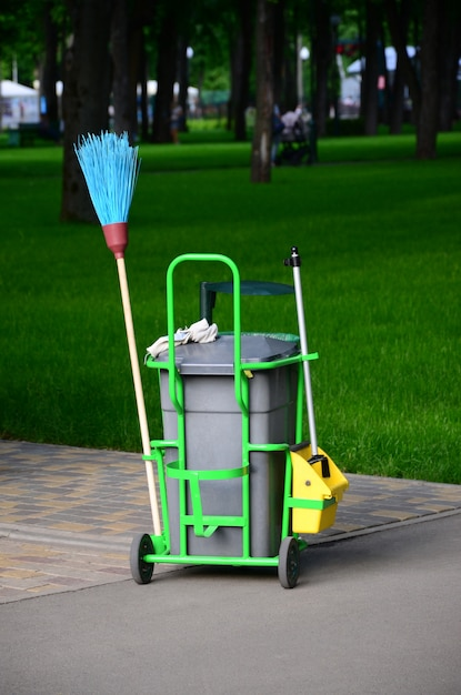 Cleaning service cart full of supplies and equipment along with grey trash bin Premium Photo