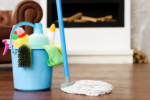 Cleaning set and products in blue bucket with mop Premium Photo