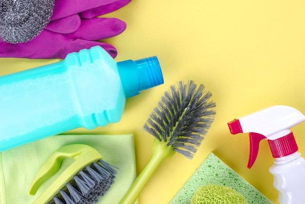 Cleaning supplies over yellow background Free Photo