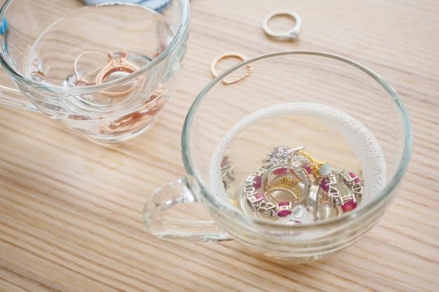 ヴィンテージジュエリーダイヤモンドリングと木製のテーブルの上のガラスのブレスレットのクリーニング Premium写真
