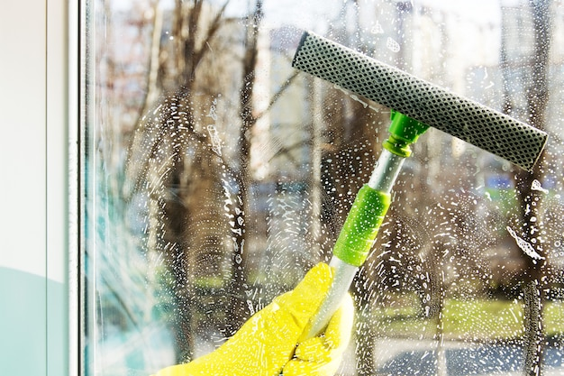 Cleaning windows with a special scraper Premium Photo
