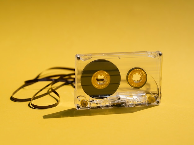 Clear broken cassette tape on yellow background Free Photo
