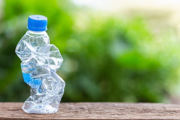 Clear empty plastic bottle on wooden table or counter with green nature light blur background Premium Photo