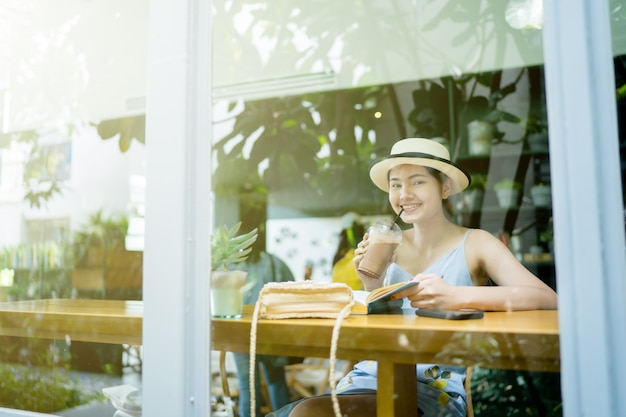 Clear glass reflection, woman sitting reading a book in a coffee shop Premium Photo