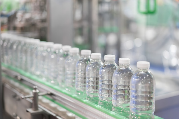 Clear water bottles transfer on conveyor belt system. Premium Photo